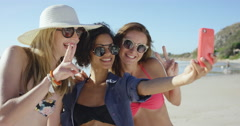 Group of girl friends taking selfies on the beach making peace sign using pink - stock footage