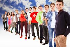 Group of unique cheerful teenagers on the background of blue sky - stock photo