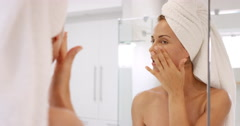 Beautiful woman applying skincare lotion to face caring for skin with feminine Stock Footage