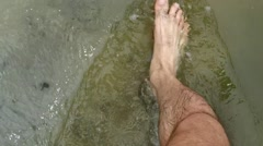 men's bare feet are on the river Bank - stock footage