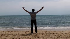 A man on the beach happy rase hands Stock Footage