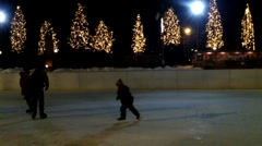 People skate on the rink in the evening amid the glowing trees Stock Footage