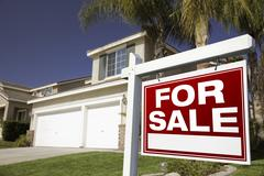 For Sale Real Estate Sign in Front of House. Stock Photos