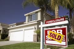 Red Foreclosure For Sale Real Estate Sign in Front of House. Stock Photos