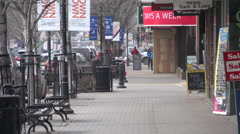 Small town shops and walk long lens Stock Footage