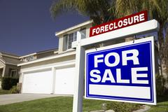 Foreclosure For Sale Real Estate Sign in Front of House. Stock Photos