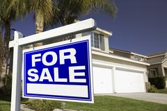 For Sale Real Estate Sign in Front of House. - stock photo