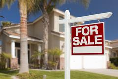 Home For Sale Real Estate Sign in Front of Beautiful New House. Stock Photos