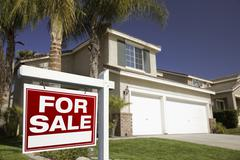 Red For Sale Real Estate Sign in Front of House. Stock Photos