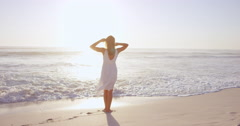 Free happy woman with arms outstretched enjoying nature walking along beach at - stock footage