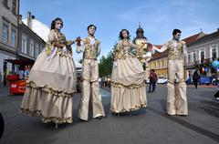 Artists on stilts performing in medieval costumes - stock photo