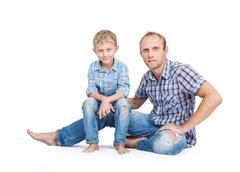 Father with son in old tattered jeans and plaid shirts on the white - stock photo