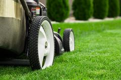 Lawn mower on green grass - stock photo