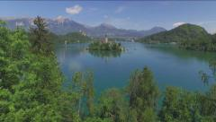 AERIAL: Flying over the trees towards the island Bled Stock Footage