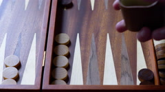 4K playing backgammon using a wooden set, rolling brown dice Stock Footage