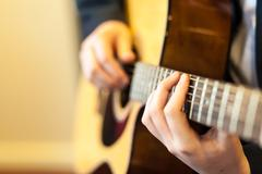 Close up of guitar playing hands - stock photo