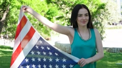 Patriotic  young woman with the American flag held in her hands dancing slowmo - stock footage