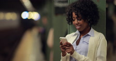 Young African American black woman at subway station texting cell phone Stock Footage