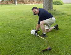 Man Starting A String Trimmer Stock Photos