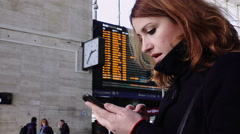 Woman texting a message and checking the train time table in the station Stock Footage