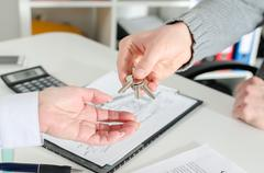 Realtor handing the keys to his client - stock photo