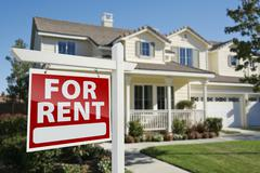 Right Facing Red For Rent Real Estate Sign in Front of Beautiful House. Stock Photos