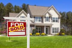 Sold Home For Sale Real Estate Sign and Beautiful New House. - stock photo