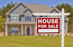 Stock Photo of Home For Sale Real Estate Sign in Front of Beautiful New House.