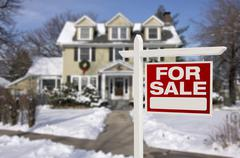 Home For Sale Real Estate Sign in Front of Beautiful New House in the Snow. - stock photo