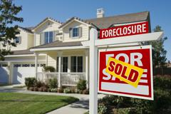 Sold Foreclosure Home For Sale Sign in Front of Beautiful House. Stock Photos