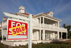 Sold Home For Sale Sign in Front of Beautiful New House. - stock photo