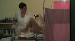 Nurse preparing pregnant woman for childbirth. Woman lying on table for birth. - stock footage
