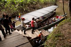 Unidentified tourists boarding a canoe in the amazon rainforest, Yasuni National - stock photo