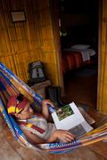 Unidentified tourist resting on a hammock in an amazon rainforest lodge - stock photo