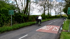 Two Cyclists on a British countryside road Stock Footage
