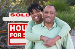 Happy African American Couple in Front of Sold Home For Sale Real Estate Sign Stock Photos