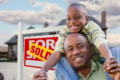 Father and Son In Front of Real Estate Sign and Home Stock Photos