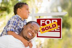 Mixed Race Father and Son In Front of Sold Real Estate Sign Stock Photos