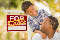 Mixed Race Father and Son In Front of Sold Real Estate Sign - stock photo