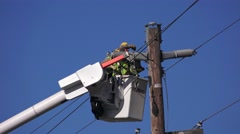 Public utility worker repairing power lines Stock Footage