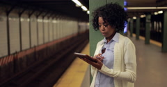 Young African American black woman at subway station using tablet pc computer - stock footage