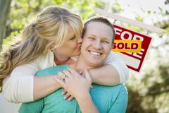Happy Couple Hug In Front of Sold Real Estate Sign. - stock photo