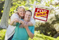 Happy Couple Holding House Keys In Front of Sold Real Estate Sign. Stock Photos