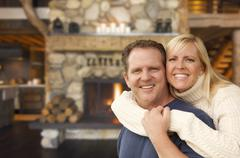 Happy Affectionate Couple at Rustic Fireplace in Log Cabin. - stock photo