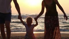 Happy Family Walking On Sea Coast. Silhouettes Sunset - stock footage