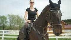 SLOW MOTION CLOSE UP: Young woman horseback riding in manege Stock Footage