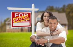 Hispanic Couple, New Home and Sold Real Estate Sign Kuvituskuvat
