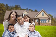 Happy Young Hispanic Family in Front of Their New Home. Stock Photos