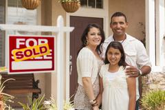 Stock Photo of Hispanic Family in Front of Their New Home with Sold Sign