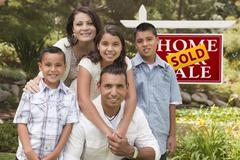 Happy Hispanic Family in Front of Sold Home for Sale Real Estate Sign. Stock Photos